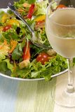 Salad. A health dinner salad with lots of greens and glass of white wine Stock Photography