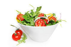 Salad. A green salad in a stylish white bowl.  With rocket leaves, cherry tomatoes, spanish onions, and capsicum Royalty Free Stock Images