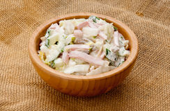 Salad. Fresh salad from ham of a cucumber of mushrooms of corn of cabbage of greens under mayonnaise in wooden ware on a cloth Royalty Free Stock Photo
