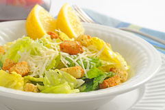 Salad. Delicious caesar salad served with wedges of lemon Royalty Free Stock Photography