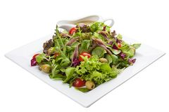 Salad with anchovies and vegetables on a white plate stock image