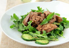 Salad appetizer with chicken liver, arugula. And cucumber royalty free stock image