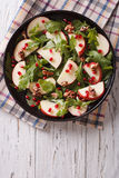 Salad with apples, pomegranates, walnut and arugula. vertical to. Salad with apples, pomegranates, walnuts and arugula on a plate. vertical top view royalty free stock photography