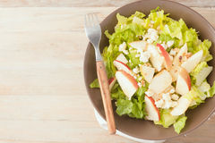 Salad with apples and walnuts on rustic wooden background Stock Photo