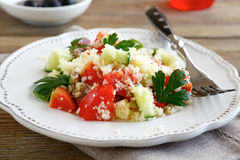 Salad with arabic couscous and vegetables on a white plate Stock Images
