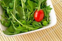 Salad with arugula and cherry tomato. (closeup royalty free stock photos