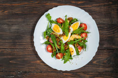 Salad with arugula, cherry tomatoes, eegs and cheese on white ceramic plate over rustic wood background, top view.  Royalty Free Stock Photos