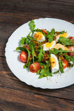 Salad with arugula, cherry tomatoes, eegs and cheese on white ceramic plate over rustic wood background, top view.  Stock Images