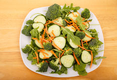 Salad of Arugula Cucumbers Broccoli and Carrots Stock Photo