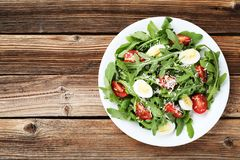 Salad with arugula leafs. Tomatoes and eggs on brown wooden table stock images
