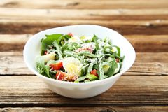 Salad with arugula leafs. Tomatoes and eggs on brown wooden table stock image