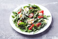 Salad with arugula leafs. Tomatoes and eggs on grey wooden table stock photo