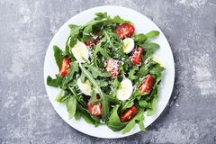 Salad with arugula leafs. Tomatoes and eggs on grey wooden table royalty free stock images