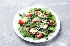 Salad with arugula leafs. Tomatoes and eggs on grey wooden table royalty free stock photos