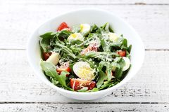 Salad with arugula leafs. Tomatoes and eggs on wooden table royalty free stock photo