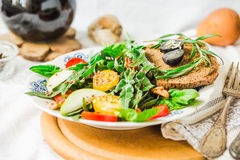 Salad with arugula, pear, tomato, olives, grapes, walnuts, close Stock Photo