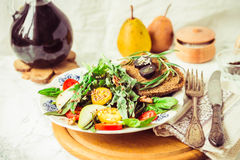 Salad with arugula, pear, tomato, olives, grapes, walnuts,tintin Stock Images