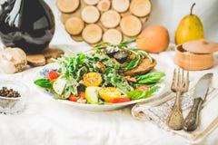 Salad with arugula, pear, tomato, olives, grapes, walnuts,tintin Stock Image