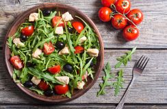 Salad with arugula. Tomatoes , olives and chicken stock image