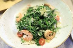 Salad with arugula and shrimps. In restaurant stock image