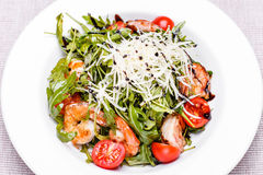 Salad with arugula and shrimps in a white plate royalty free stock image