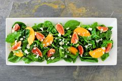 Salad of arugula, spinach, figs and cheese in a white rectangular plate over slate. Autumn salad of arugula, spinach, figs and goat cheese in a white rectangular Stock Photo