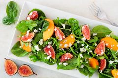Salad of arugula, spinach, figs and cheese in a white rectangular plate, overhead on marble. Autumn salad of arugula, spinach, figs and goat cheese in a white Stock Photo
