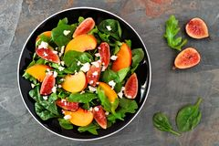 Salad of arugula, spinach figs and goat cheese, above view on slate. Autumn salad of arugula, spinach figs and goat cheese in a black plate, above view on a Royalty Free Stock Photo