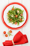Salad with arugula, tomatoes cherry and mozzarella on white and Stock Photo
