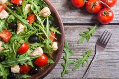 Salad with arugula. Tomatoes , olives and chicken stock photos