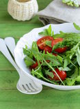 Salad with arugula and tomatoes on a wooden table Stock Photo