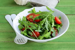 Salad with arugula and tomatoes on a wooden table Royalty Free Stock Image