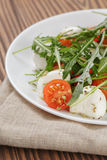 Salad from arugula tomatos and baby mozzarella. On wood table royalty free stock photos