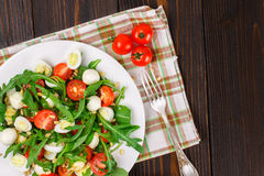 Salad with arugula on a wooden background Stock Image