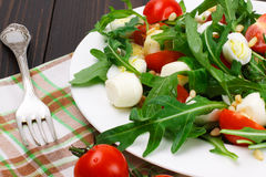 Salad with arugula on a wooden background Royalty Free Stock Photo