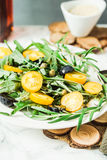 Salad with arugula, yellow tomatoes,grapes, sesame, tinting. Fresh green salad with arugula, yellow tomatoes, olives, grapes and sesame,healthy lifestyle and raw Royalty Free Stock Photos