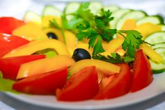 Salad of assorted vegetables in a plate stands on a festive table. Red tomatoes, cucumbers, olives, yellow pepper, parsley royalty free stock images