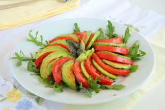 Salad with avocado. And tomatoes and arugula on a plate stock images