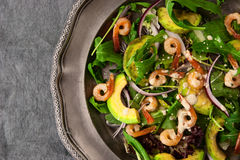 Salad with avocado , arugula and shrimps on the vintage metal plate  close-up Royalty Free Stock Photo