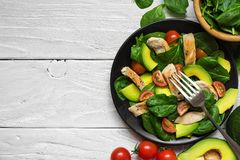 Salad with avocado, chicken, spinach and tomatoes cherry in black plate with fork stock photo
