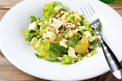 Salad with Avocado, Lettuce, Orange and Nuts on a white bowl Royalty Free Stock Photos