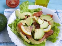 Salad with avocado natural red fish vegetable dinner on blue wooden lemon. Salad with avocado red fish oil  dinner on blue wooden lemon vegetable natural Royalty Free Stock Photography