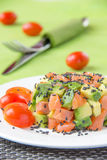 Salad with avocado and red fish. On white plate Stock Photos