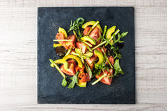Salad with avocado , trout and asparagus on the black stone top view Royalty Free Stock Image