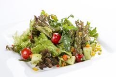 Salad with avocado and vegetables on a white plate stock images