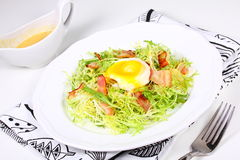Salad with bacon and eggs poached. Stock Images
