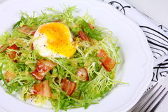 . Salad with bacon and eggs poached. Stock Images