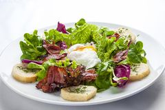 Salad with bacon and poached egg on a white plate royalty free stock photo