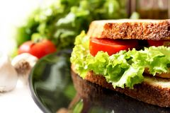 Salad, bacon and tomato sandwich. Sandwich with tomato slices, salad and bacon placed on a plate, with garlic and tomatoes in the background Stock Photos