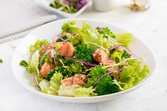 Salad of baked fish salmon, broccoli, lettuce, red onion and dressing. Fish menu.